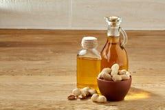 Óleo aromático em um frasco e em uma garrafa de vidro com os pistacios na bacia na tabela de madeira, close-up Fotografia de Stock Royalty Free