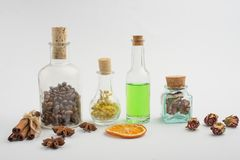Óleo aromático, grãos de café, ervas do aroma nas garrafas de vidro, em um fundo claro O conceito do cuidado e da beleza do corpo fotografia de stock royalty free