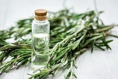 Óleo cosmético natural com alecrins frescos no fundo de madeira claro da tabela imagem de stock royalty free