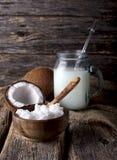 Óleo de coco com leite de coco no vidro em um fundo de madeira fotografia de stock
