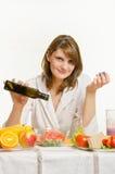 Óleo de derramamento da jovem mulher em uma salada do vegetal do vegetariano Fotografia de Stock