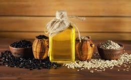 Óleo de girassol e sementes de girassol no fundo de madeira foto de stock royalty free