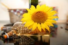 Óleo de girassol em uma garrafa de vidro com sementes naturais e uma flor do girassol imagens de stock royalty free