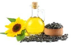 Óleo de girassol no jarro, nas sementes de vidro e na flor isolados no fundo branco Imagens de Stock
