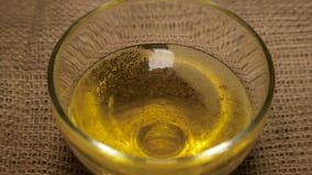 Óleo de semente do girassol em um close-up da bacia de vidro vídeos de arquivo