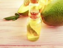 Óleo, nutriente fresco do verão do abacate em um fundo de madeira em um fundo de madeira imagens de stock royalty free