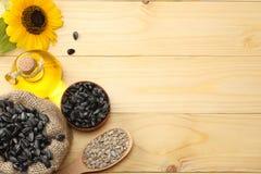Óleo, sementes e flor de girassol no fundo de madeira claro Vista superior com espaço da cópia Fotografia de Stock