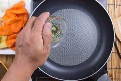 Óleo vegetal de derramamento do cozinheiro chefe à bandeja Foto de Stock