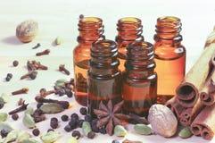 Óleos essenciais nas garrafas de vidro e nas especiarias no fundo de madeira com copyspace imagem de stock