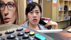 Óptico de la mujer que da la información sobre la visión del ojo para el cliente almacen de video