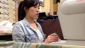Óptico de la mujer que prueba la visión masculina del ojo almacen de metraje de vídeo