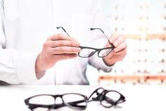 Óptico en la tienda que sostiene los vidrios Oculista con las lentes foto de archivo