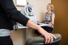 Óptico feliz Asking Patient To Sit In Store imagen de archivo