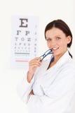 Óptico femenino magnífico con una prueba del ojo Fotografía de archivo libre de regalías
