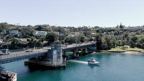 Órbita aérea de un puente con el barco que pasa debajo de tráfico Puente del escupitajo almacen de metraje de vídeo