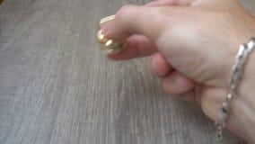 Órbita de la persona agitada del oro nuevo, haciendo girar en la mano de un hombre joven en fondo gris almacen de metraje de vídeo