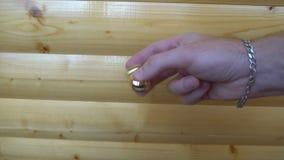 Órbita de la persona agitada del oro nuevo, haciendo girar en la mano de un hombre joven en fondo de madera almacen de metraje de vídeo