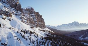 Órbita lateral aérea al valle nevoso con el bosque de maderas en el paso de Falzarego Puesta del sol o salida del sol, cielo clar metrajes