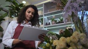 Órdenes sonrientes de la flor de la ojeada del florista en línea almacen de video
