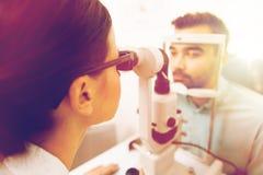 Ótico com lâmpada e o paciente cortados na clínica de olho foto de stock
