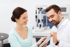 Ótico com PC e paciente da tabuleta na clínica de olho fotografia de stock royalty free