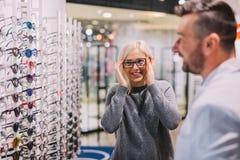 Ótico e cliente que escolhem vidros junto fotos de stock
