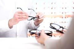 Ótico e cliente que escolhem vidros novos fotografia de stock royalty free