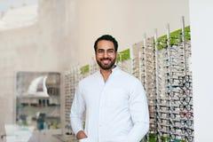 Ótico Man Near Showcase com os monóculos na loja dos vidros foto de stock royalty free