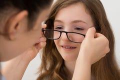 Ótico Putting Eyeglasses On um paciente fotos de stock