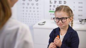 Ótico que dá a cenoura à criança alegre, nutrição saudável da vitamina para os olhos filme