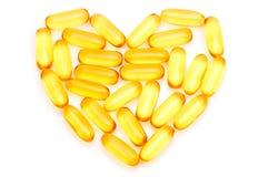 Ômega do óleo de fígado de bacalhau 3 cápsulas do gel sob a forma do coração no branco fotos de stock