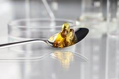 Ômega dos comprimidos das vitaminas da colher 3 suplementos com prato de petri Imagem de Stock Royalty Free