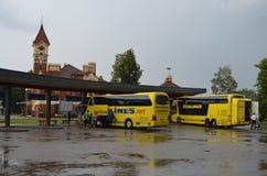 Ônibus amarelos de Ecolines em um dia de verão nublado em uma estação em Mariampol, Letónia imagem de stock royalty free