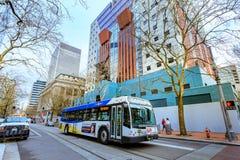 Ônibus de corrida de TriMet na frente da construção de Portland em Por do centro imagens de stock