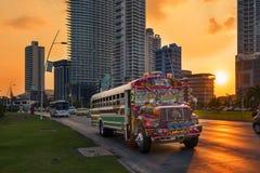 Ônibus do diabo vermelho na Cidade do Panamá com construção moderna no fundo no por do sol, em Panamá Foto de Stock Royalty Free
