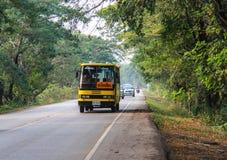 Ônibus escolar amarelo na estrada em Tailândia Imagem de Stock