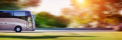 Ônibus na estrada asfaltada no dia de mola bonito Fotografia de Stock