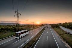 Ônibus que viaja em uma estrada só no por do sol bonito foto de stock