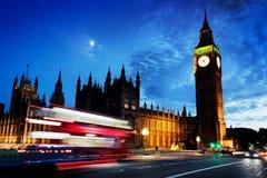Ônibus vermelho, Big Ben e palácio de Westminster em Londres, o Reino Unido na noite Lua que brilha foto de stock