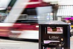 Ônibus vermelho e branco que passa ao longo da rua em um borrão com uma cesta de lixo no primeiro plano fotos de stock royalty free