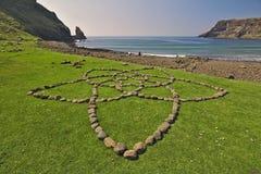 Ö av Skye, Skottland - stenar som är ordnade i formen av en blomma på grönt gräs med Talisker, skäller i bakgrunden Arkivfoto