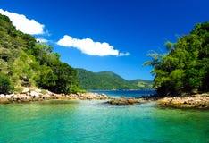 Ö, grönt hav och blå himmel arkivfoto