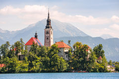 Ö med katolska kyrkan på den blödde sjön i Slovenien med Mounta Arkivbilder