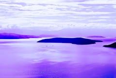 Öar med ett hav med purpurfärgade reflexioner royaltyfria foton