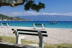 Öde bänkar på den Baska stranden Arkivfoton