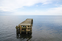 Öde brygga som omges av vattnet Royaltyfri Bild