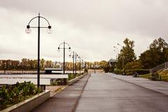 Öde invallning av floden, rytmen av ljusen och utsikten av den tidiga hösten för väg per molnig morgon Royaltyfri Fotografi