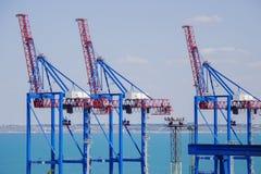 Öde portterminal i en hamn för ladda och offloading lastfartyg och frakter med rader av stora industriella kranar till lif Royaltyfri Bild