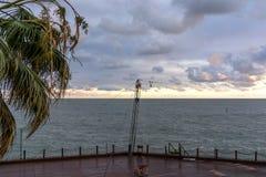 Öde promenad som förbiser havet och en ensam palmträd Royaltyfri Fotografi