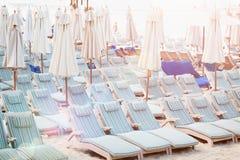 Öde strand med överflöd av strandstolar ay solnedgång, begrepp av avkopplad fritid Royaltyfria Foton